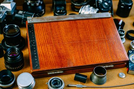 Retro mockup. Closeup old wood equipment for cut fotographic paper in center of retro vintage photographic accessories and quipments around on wooden Background. Top view 版權商用圖片