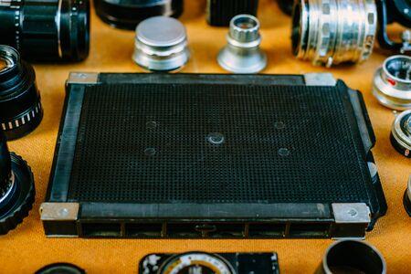 Retro mockup. Closeup black retro plastic box for film in center of retro vintage photographic accessories and quipments around on wooden Background.