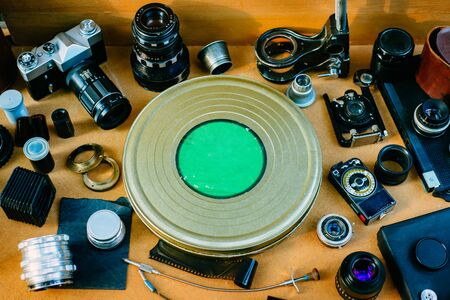 Retro photographic mockup. Metal round box from film in center and vintage photographic accessories and quipments around on Wooden Background. 版權商用圖片
