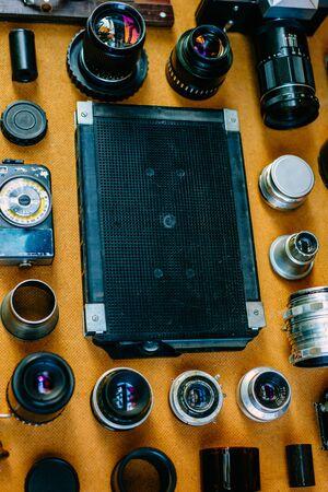 Retro mockup. Closeup black retro plastic box for film in center of retro vintage photographic accessories and quipments around on wooden Background. Vertical photo
