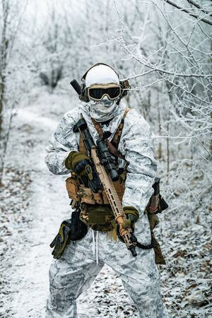 Airsoft man in white camouflage uniform and machinegun with optical sight. Soldier in the winter forest territory background. Vertical photo