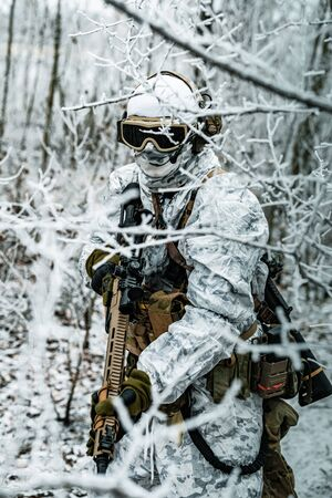 Airsoft man in white camouflage uniform and machinegun with optical sight. Soldier in the winter forest between branches. Vertical photo.