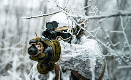Airsoft man in white camouflage uniform aims at the sight. Soldier in the winter forest between branches. Horizontal photo. Stock Photo