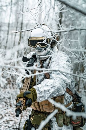Airsoft man in white camouflage uniform and machinegun with optical sight. Soldier in the winter forest between branches. Vertical photo Stock Photo - 142073190