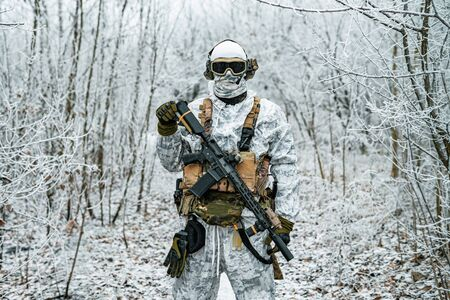 Military man in white camouflage uniform with machinegun. Soldier in the winter forest territory background. Horizontal photo