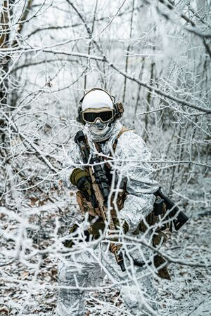 Airsoft man in white camouflage uniform and machinegun with optical sight. Soldier in the winter forest between branches. Vertical photo