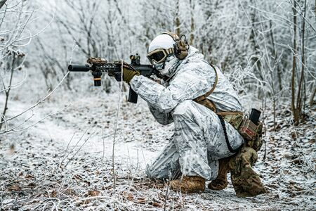Airsoft man in white camouflage uniform with machinegun. Soldier  stood on knelt in the winter forest and aims at the sight of the machinegun. Side view