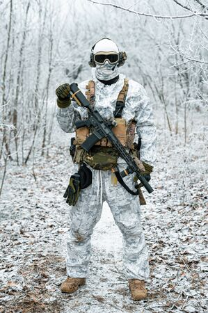 Military man in white camouflage uniform with machinegun. Soldier in the winter forest territory background. Vertical photo Stock Photo - 142073317