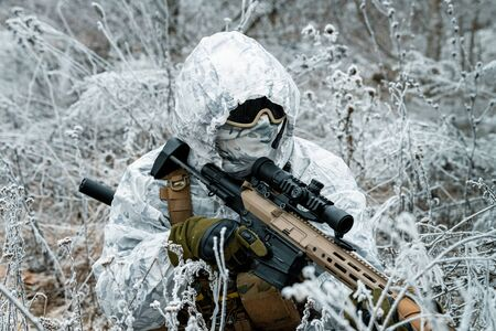 Closeup military man in white camouflage uniform with hood and machinegun in the long winter grass. Soldier stood on knelt with machinegun.