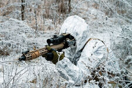 Military man in white camouflage uniform with hood and machinegun in the long winter grass. Soldier stood on knelt and aims of the machinegun. Stock Photo