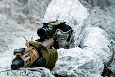 Closeup military man in white camouflage uniform with hood and machinegun in the long winter grass. Soldier stood on knelt with machinegun. Horizontal photo Stock Photo