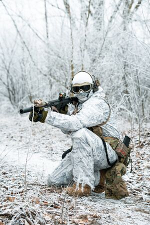 Airsoft man in white camouflage uniform with machinegun. Soldier with muchinegun stood on knelt in the winter forest. Vertical photo, side view