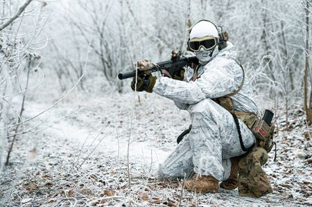 Airsoft man in white camouflage uniform with machinegun. Soldier with muchinegun stood on knelt in the winter forest. Horizontal photo, side view
