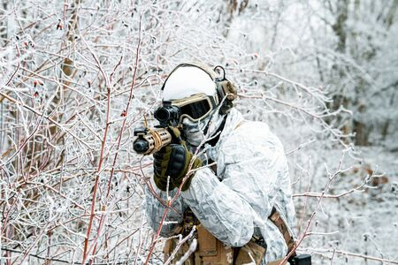 Closeup military man in white camouflage uniform with machinegun. Soldier  in the winter forest and aims at the sight of the machinegun. Front view