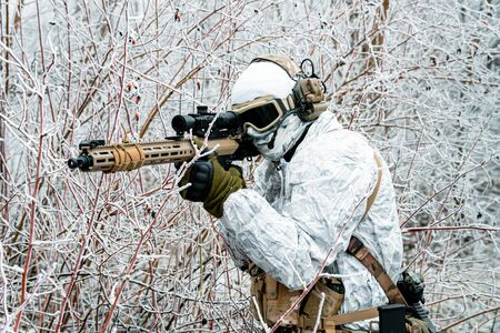 Closeup military man in white camouflage uniform with machinegun. Soldier  in the winter forest and aims at the sight of the machinegun. Side view Stock Photo - 142073486
