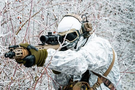 Closeup military man in white camouflage uniform with machinegun. Soldier in the winter forest and aims at the sight of the machinegun. Side view