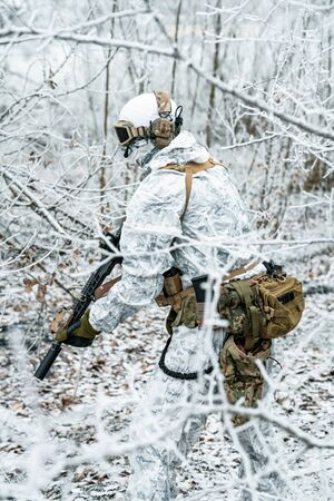 Airsoft man in white camouflage uniform and machinegun. Soldier in the winter forest between branches. Vertical photo side view