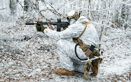 Airsoft man in white camouflage uniform with machinegun. Soldier  stood on knelt in the winter forest and aims at the sight of the machinegun. Side view Stock Photo - 142073539