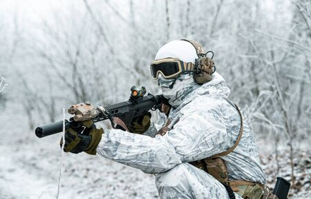 Airsoft man in white camouflage uniform with machinegun. Soldier with muchinegun stood on knelt in the winter forest. Side view