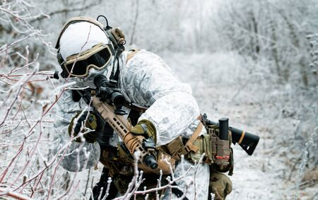Closeup military man in white camouflage uniform with machinegun. Soldier sneaking in the winter forest with machinegun. Front view