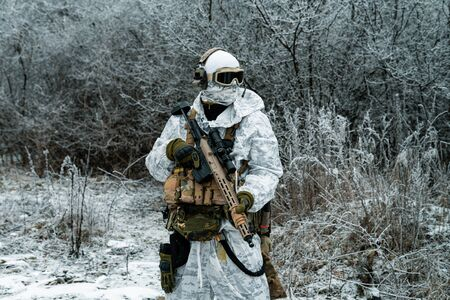Military man in white camouflage uniform with machinegun. Soldier in the winter forest territory background. Horizontal photo Stock Photo - 142073546