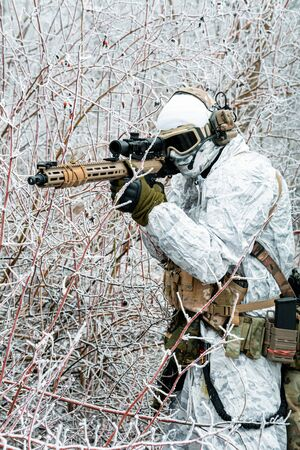 Military man in white camouflage uniform with machinegun. Soldier  in the winter forest and aims at the sight of the machinegun. Side view