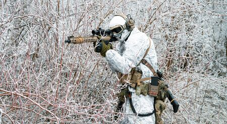 Airsoft man in white camouflage uniform with machinegun. Soldier  in the winter forest and aims at the sight of the machinegun. Side view Stock Photo - 142073553