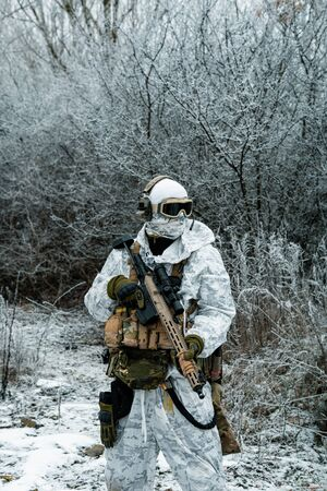 Military man in white camouflage uniform with machinegun. Soldier in the winter forest territory background. Stock Photo - 142073574