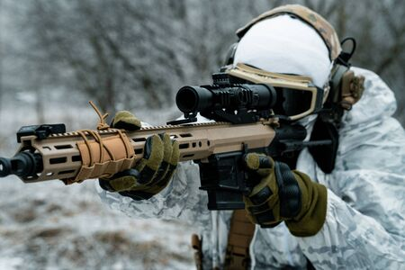 Closeup military man in white camouflage uniform with machinegun. Soldier aims of the machinegun. Stock Photo