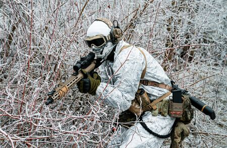 Military man in white camouflage uniform with machinegun. Soldier sneaking in the winter forest with machinegun. Side view