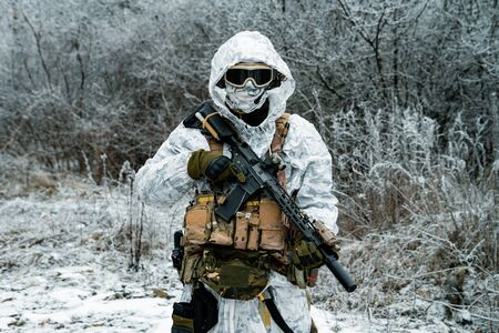 Military man in white camouflage uniform with hood and machinegun. Soldier in the winter forest territory background. Horizontal photo Stock Photo