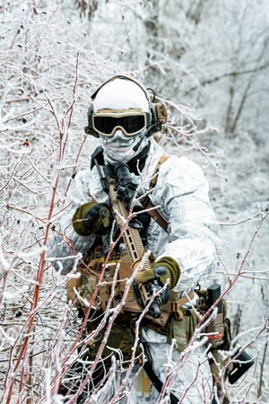 Military man in white camouflage uniform with machinegun. Soldier in the winter forest territory background. Vertical photo Stock Photo