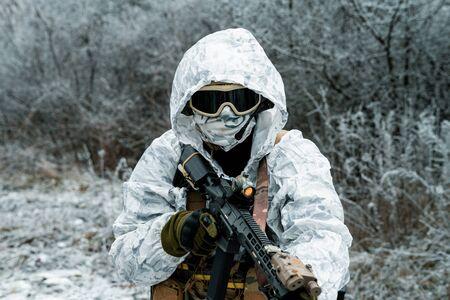 Closeup military man in white camouflage uniform with hood and machinegun. Horizontal photo
