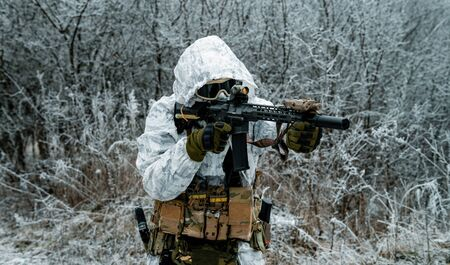 Closeup military man in white camouflage uniform with hood and aims of the machinegun. Horizontal photo side view Stock Photo