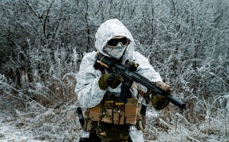 Military man in white camouflage uniform with hood and machinegun. Soldier in the winter forest. Side view Stock Photo
