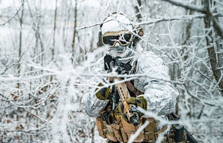 Airsoft man in white camouflage uniform and machinegun with optical sight. Soldier in the winter forest between branches. Horizontal photo Stock Photo