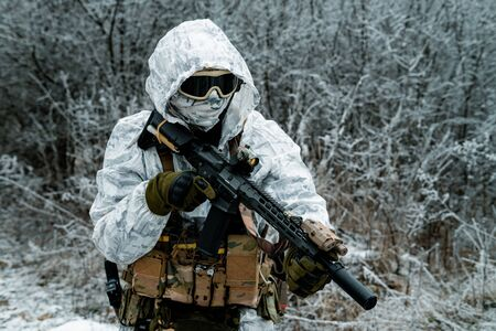 Closeup military man in white camouflage uniform with hood and machinegun. Horizontal photo side view
