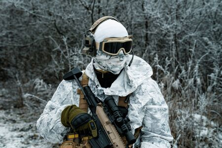 Closeup military man in white camouflage uniform with machinegun. Stock Photo - 142073675