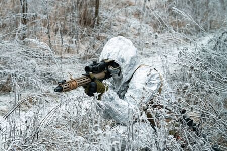 Military man in white camouflage uniform with hood and machinegun in the long winter grass. Soldier stood on knelt and aims of the machinegun.