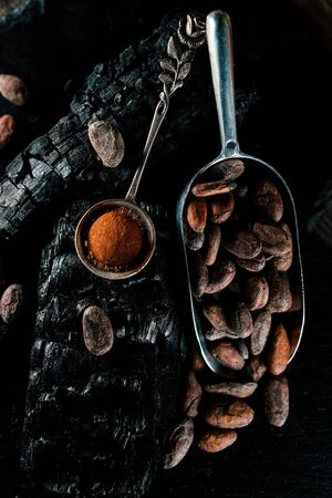 Handmade chocolate candies lay on cocoa powder in spoon on smut. Truffles lay on charcoal on blackstone stand