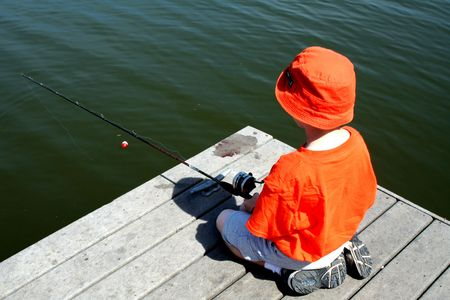 bobber: Boy fishing from dock with bobber and worm in the lake