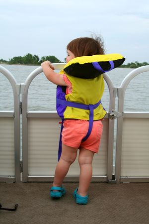 Toddler aged girl wearing a life jacket on a deck boat while on a lake photo