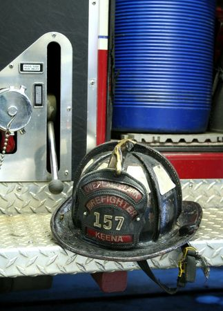 Zwarte brandweerman helm zitten op een stap van een brand vrachtwagen Stockfoto