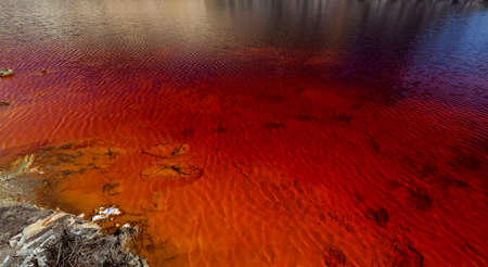 landfills: Red artificial lake and hills as a result of mining and production of copper