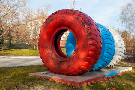 dumper: Dumper truck tires of different sizes placed as a monument in the industrial city