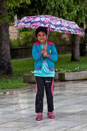 umbrela: Pavlikeni, Bulgaria - 21.6.2015.: Little girl under umbrella Editorial