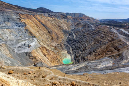 tailings: Bor, Serbia - April 15.2015: Panorama of the open pit. The copper mine Veliki Krivelj next to Bor, Serbia. Floors resulting exploitation. Tailings and copper ores. Excavators, drilling machines and dumpers for transportation of the ore material. Stock Photo