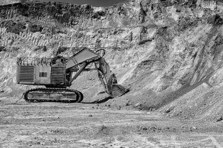 tailings: Bor, Serbia - April 15.2015: A large excavator at opencast mine.  The copper mine Veliki Krivelj next to Bor, Serbia. Floors resulting exploitation. Tailings and copper ores. Excavators, drilling machines and dumpers for transportation of the ore material Stock Photo