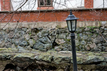 crooked: Crooked street lamp in front of a brick building Stock Photo