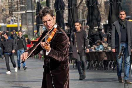 finger bow: Belgrade, Serbia - February 27, 2016: Violinist playing in the street. A street musician who plays in a busy pedestrian street in the heart of Belgrade